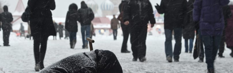 A woman begs for money during heavy snowfall in central Moscow, December 21, 2010.  REUTERS/Nikolay Korchekov  (RUSSIA - Tags: CITYSCAPE ENVIRONMENT SOCIETY IMAGES OF THE DAY) - RTXVXK9